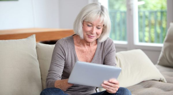 Senior woman smiles while using tablet computer at home