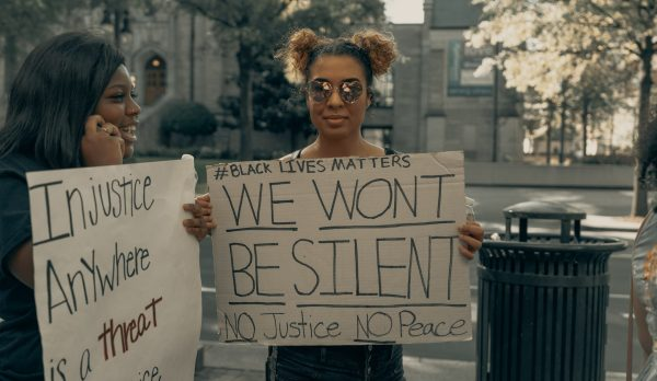"Two African American women stand holding signs protesting for racial justice. One reads ""We won't be silent. No justice, No Peace."""