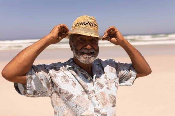 An older man adjusts his hat on a beach, looking retired