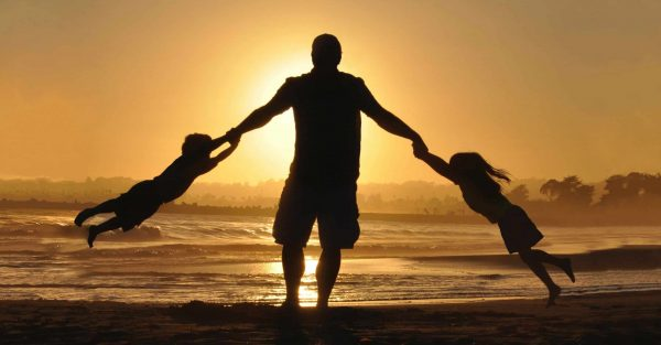 a man stands on the beach at sunset twirling two kids in his outstretched arm. he is in silhouette. the article is on balancing saving for your kids college with your own retirement.