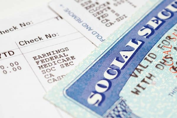 a social security card lays over documents filled with numbers in an article about claiming social security