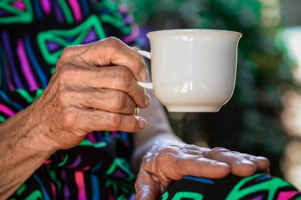 a closeup shot of an elderly woman's hands grasping a tea cup in a story about planning for risks in retirement